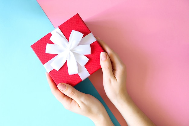 Woman holding red gift box on color blue and pink surface.