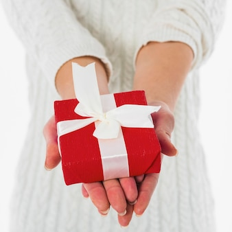 Woman holding red gift box in hands