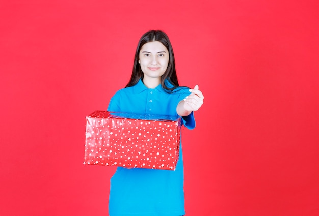 Woman holding a red gift box with white dots on it and asking for payment.