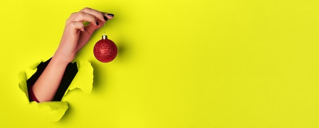 Woman holding red glittering christmas ball in hand over yellow background
