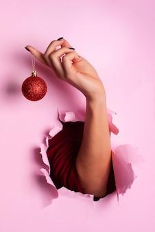 Женщина, держащая красный блестящий рождественский бал в руке на розовом фоне со снегом, светло-боке.