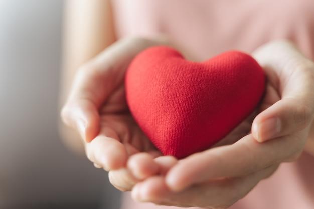 Женщина держит красное сердце любовь пожертвование медицинского страхования счастливого благотворительного добровольца психического здоровья