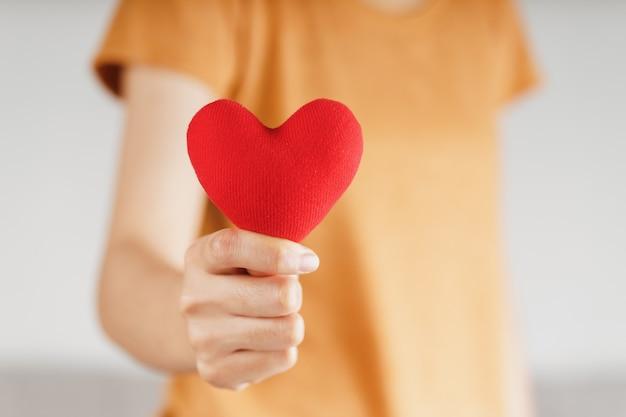 Женщина, держащая красное сердце, любовь, медицинское страхование, пожертвование, счастливый благотворительный волонтер, всемирный день психического здоровья, всемирный день сердца, день святого валентина