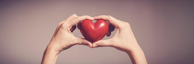 Женщина держит красное сердце, всемирный день сердца