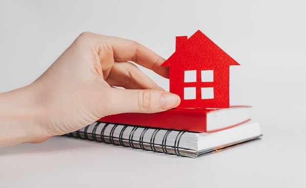 Woman holding red house with her hands on notepads