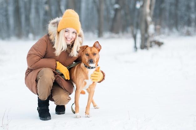 冬の森で赤い雑種犬を保持している女性。