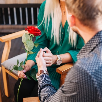 Woman holding red rose holding her boyfriend's hand