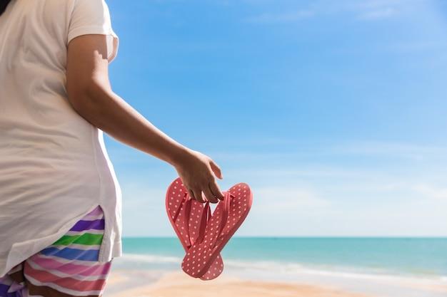 ビーチで赤いスリッパを保持している女性