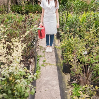Woman holding red watering can near many plants in greenhouse