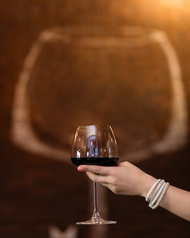 Woman holding red wine glass with glass shape