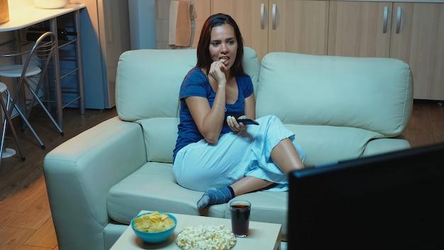 リモコンを持って、リビングルームのソファでリラックスしてポップコーンを食べる女性。テレビチャンネルを変更する快適なソファに横たわっているテレビを見て休んでいるパジャマの夜遅くに孤独な幸せな女性。
