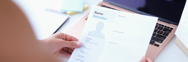 Woman holding resume for employment in her hands in front of laptop closeup