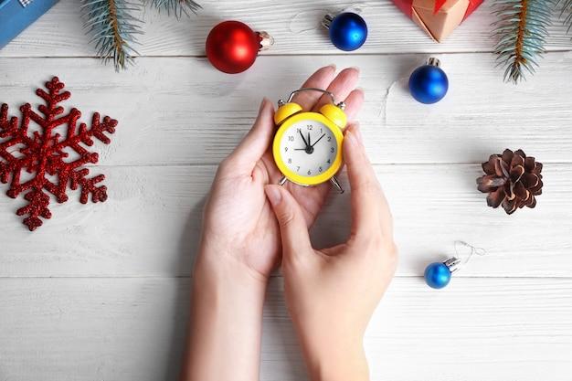 나무 테이블에 복고풍 알람 시계를 들고 여자입니다. 크리스마스 카운트다운 개념
