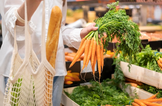 Woman holding reusable bag and carrots in grocery store