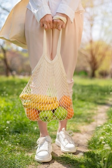 自然の中で食物と一緒に再利用可能なバッグを保持している女性