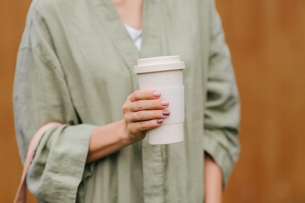 Женщина, держащая многоразовую кофейную чашку. экологичная концепция.