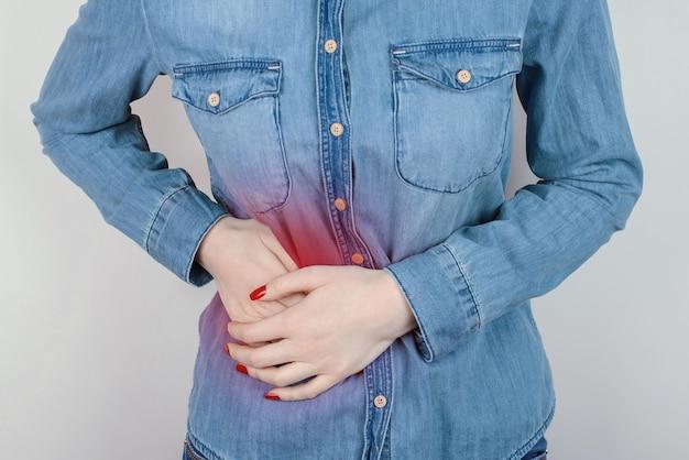 腹部の右側を保持している女性