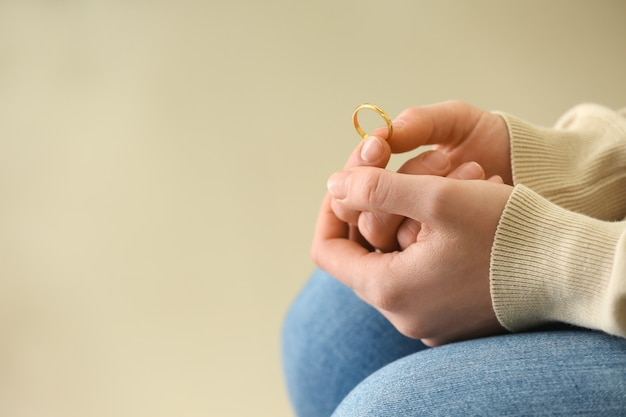 Woman holding ring, closeup. concept of divorce