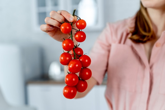 Woman holding ripe cherry tomatoes in hands. kitchen background. cropped image. healthy food.