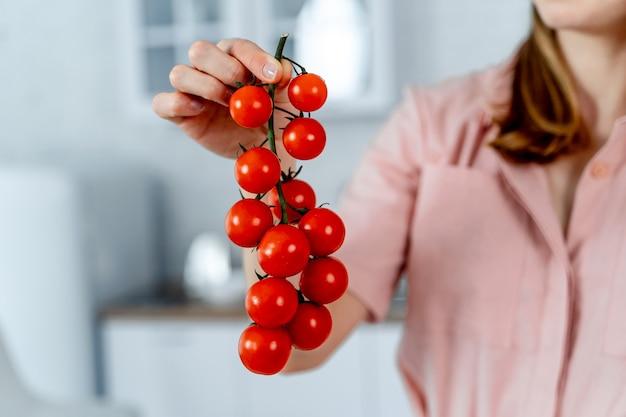 完熟チェリートマトを手に持った女性。キッチンの背景。トリミングされた画像。健康食品。