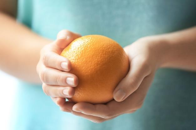 Женщина, держащая спелый апельсин, крупным планом