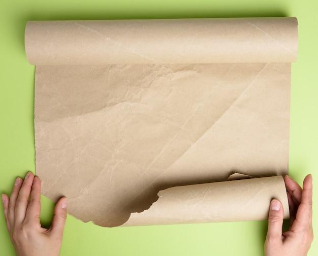Женщина держит рулон коричневой бумаги