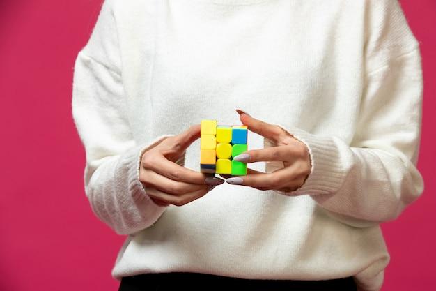 Женщина держит в руках кубик рубика