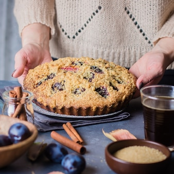 Woman holding a rustic plum cake on dark concrete background. sweet fruits pie.