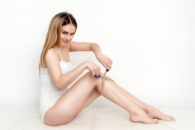 Женщина, держащая ножницы возле ее ног на белом фоне
