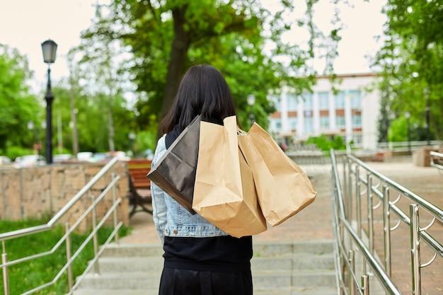 Женщина, держащая несколько бумажных пакетов, гуляет на открытом воздухе в парке