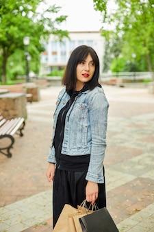 Женщина, держащая несколько бумажных пакетов с покупными вещами, гуляет на открытом воздухе в парке, девушка после покупок.