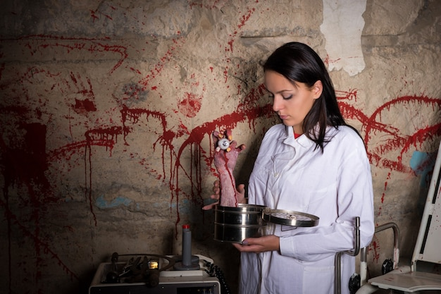 Woman holding a severed hand and eyeball in a box in front of a blood splattered wall, halloween concept