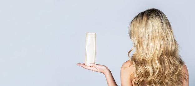 Женщина, держащая бутылку шампуня. красивая блондинка с бутылкой шампуней в руках.