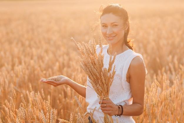 農業分野で小麦の穂の束を保持している女性