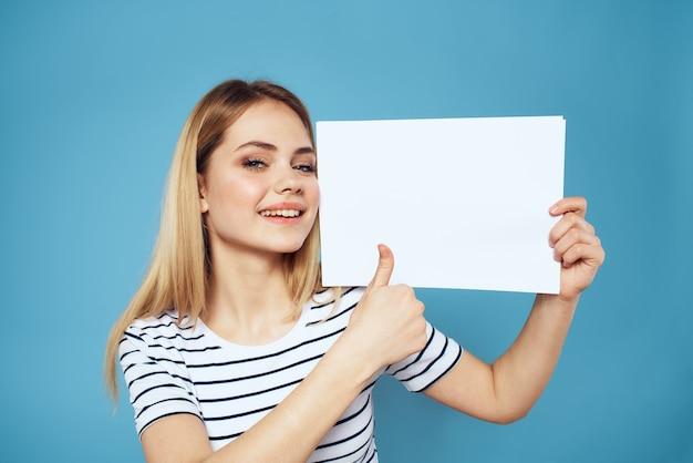 分離された紙の縞模様のtシャツのシートを保持している女性