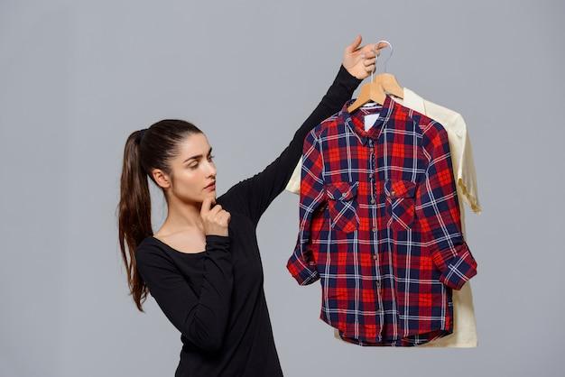 어떤 옷을 입고 선택 셔츠를 들고 여자
