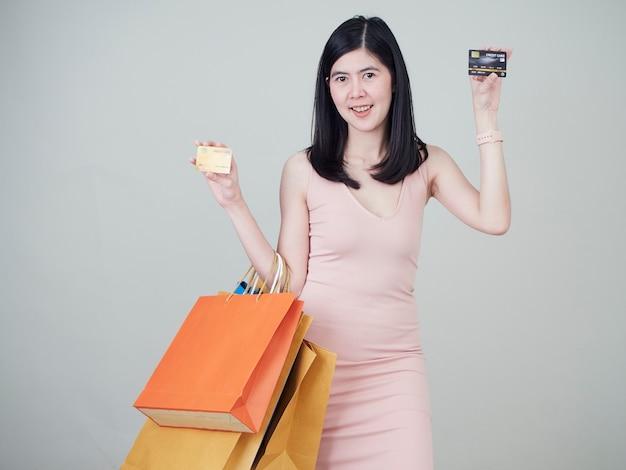 ショッピングバッグとクレジットカードを保持している女性