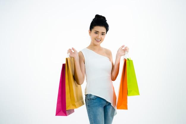 白い背景にショッピングバッグを持っている女性。