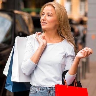 Donna che mantiene le borse della spesa dopo la sessione di vendita