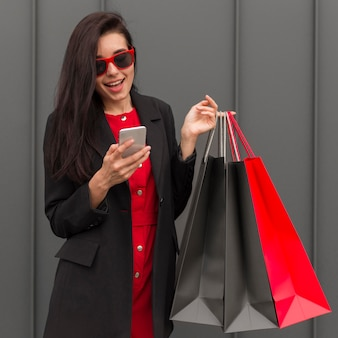 買い物袋を保持していると電話を見て女性