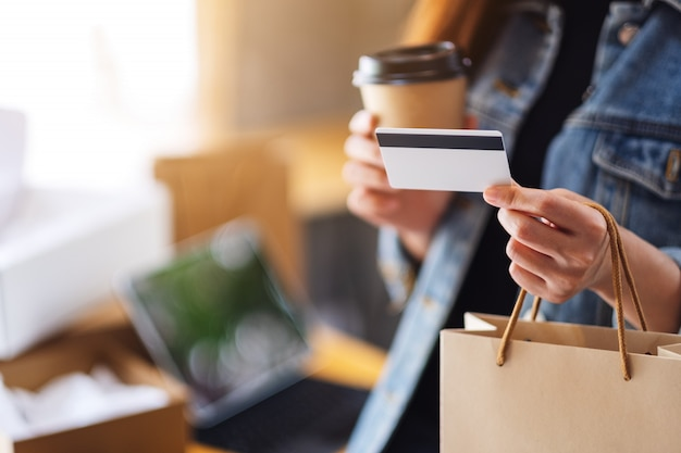 A woman holding shopping bags , credit card and coffee cup for online shopping concept