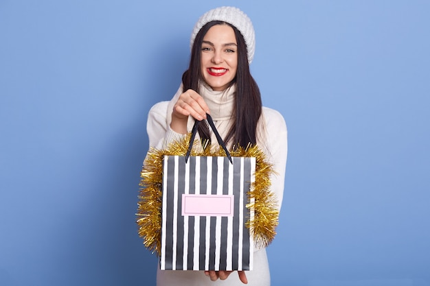 Woman holding shopping bags decorated with tinsel against blue space