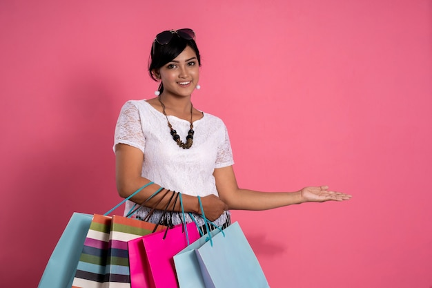 Woman holding shopping bags and hand presenting gesture