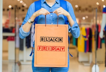 Woman holding shopping bags in the shopping mall with Black Friday concept.
