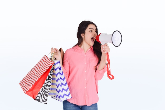 Woman holding shopping bags and megaphone