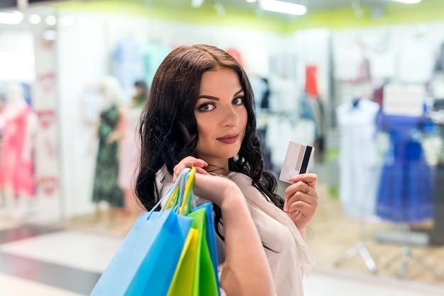 肩に買い物袋とクレジットカードを持っている女性