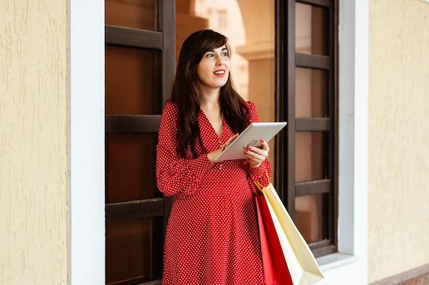 Donna che mantiene i sacchetti della spesa e tablet