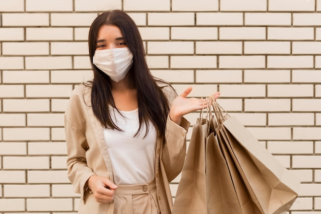 Woman holding shopping bags and wearing mask