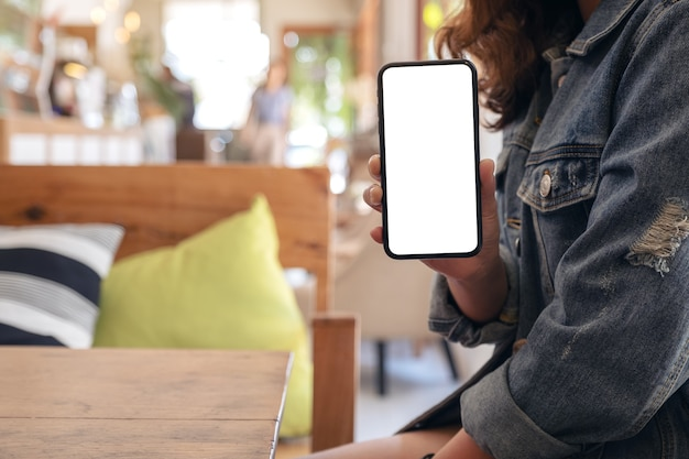 Woman holding and showing black mobile phone with blank white screen on the table in modern cafe