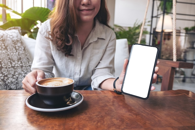 Woman holding and showing black mobile phone with blank white screen while drinking coffee in cafe